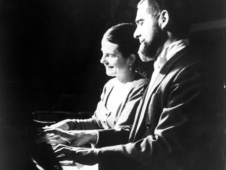 Black and white photo of two people playing piano
