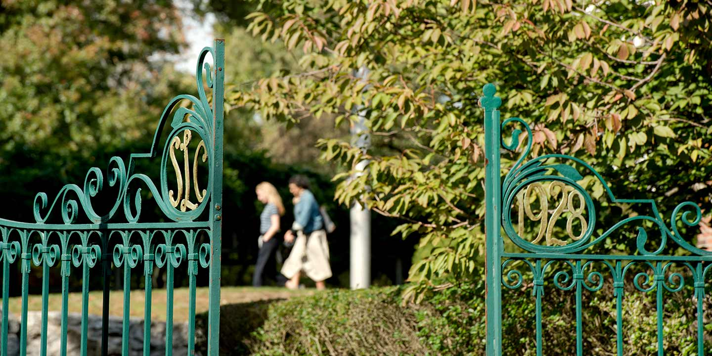Picture of Westlands Gate showing SLC 1928 in the wrought iron work with students walking in the background