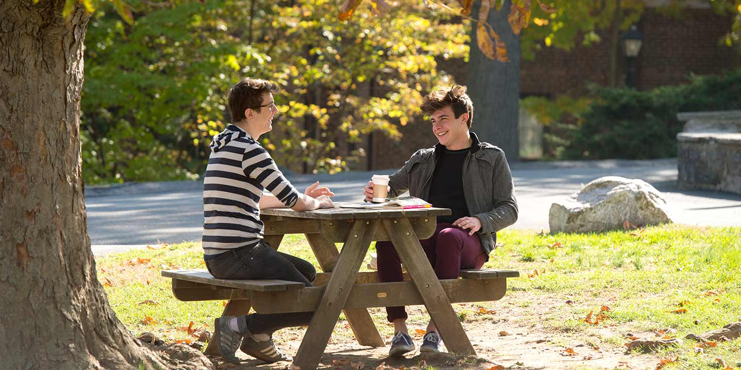 Students sitting at picnic table in discussion