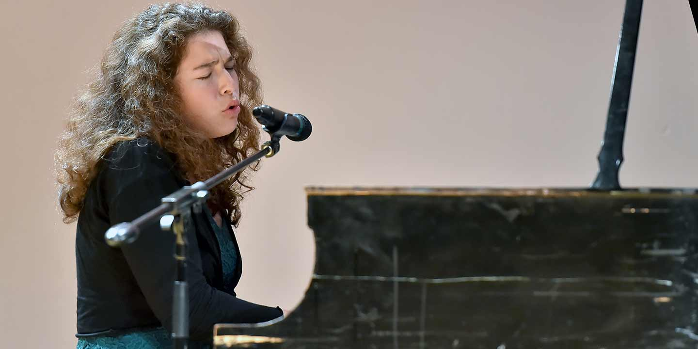 Student performing vocals and playing piano