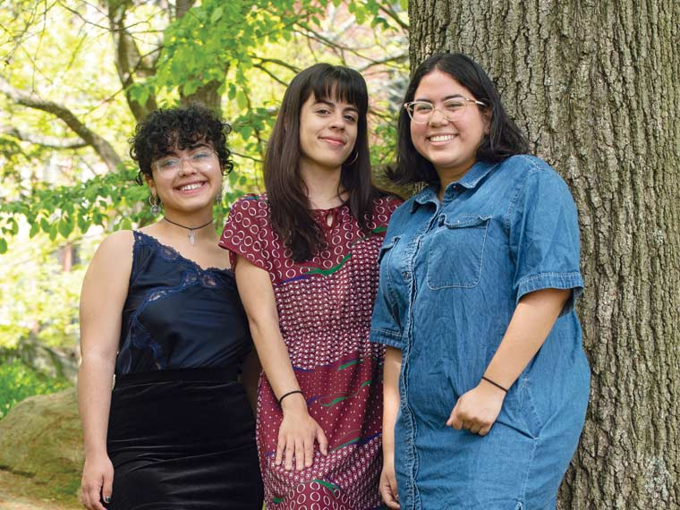 Photo o three people standing together outside near a tree.