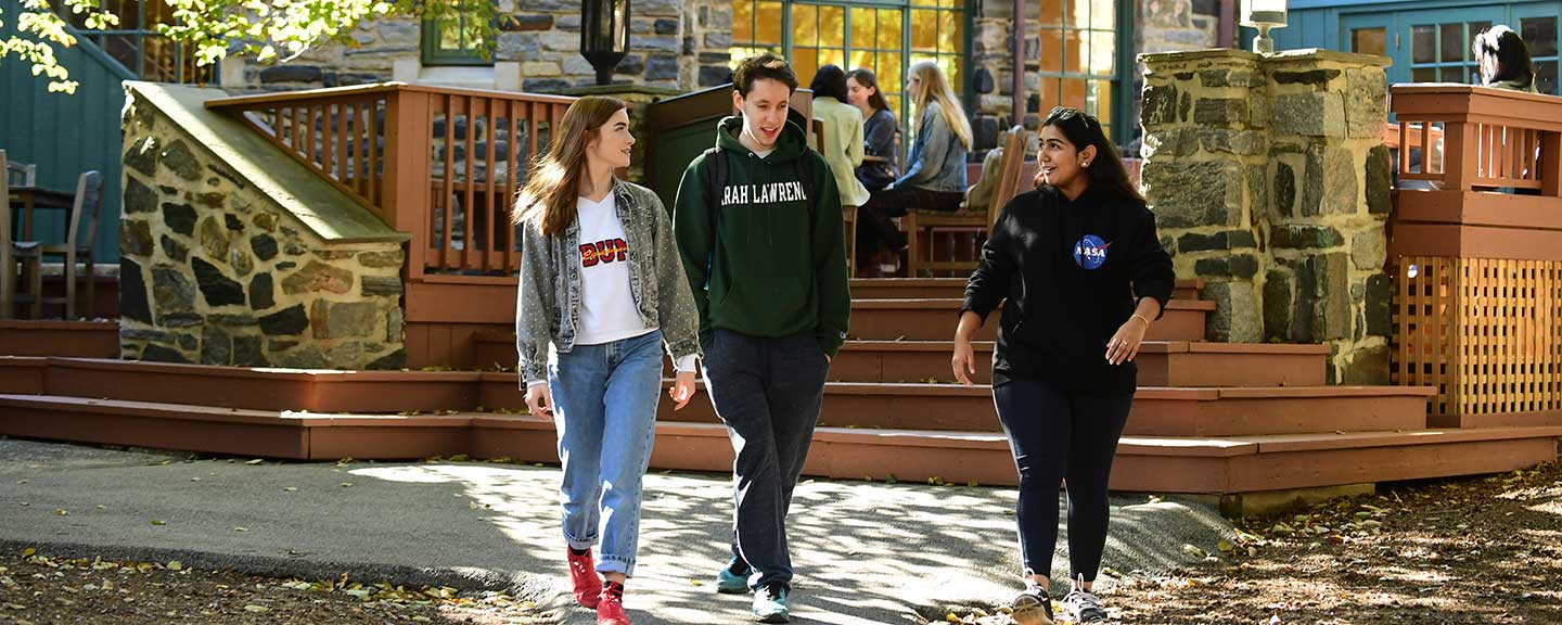 Three students walking and talking outside the Pub