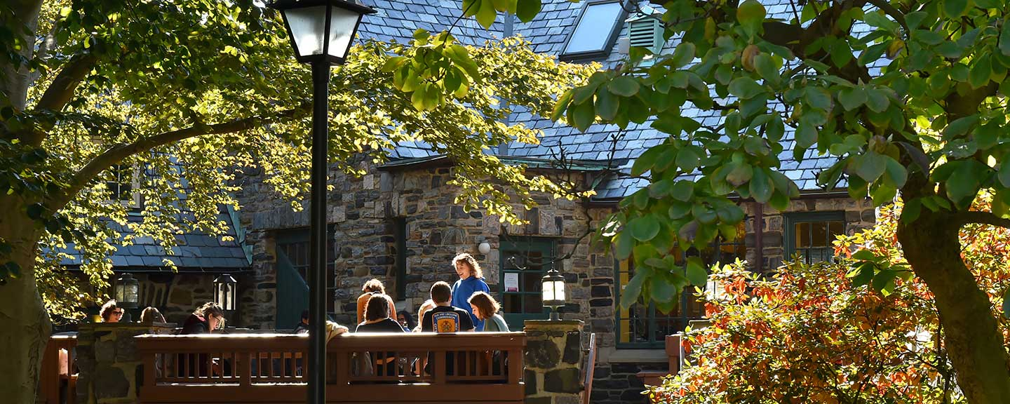 A group of students chat in the sun on the terrace of the Pub