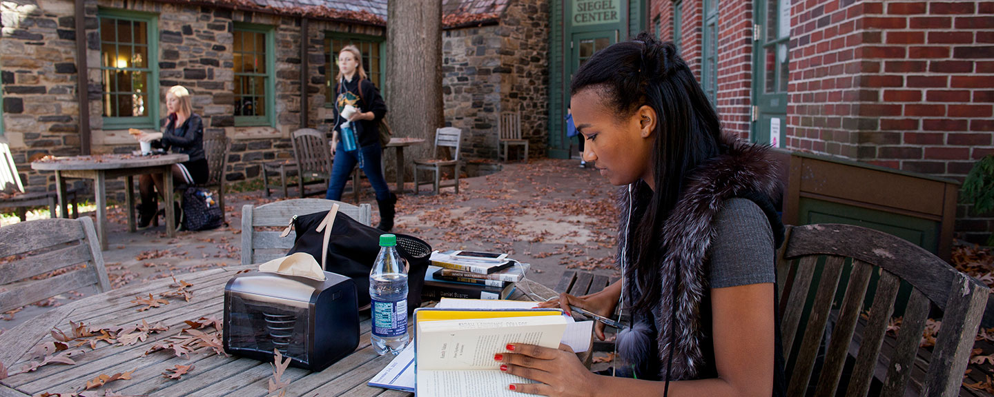 A student studies outside on the terrace at the Pub