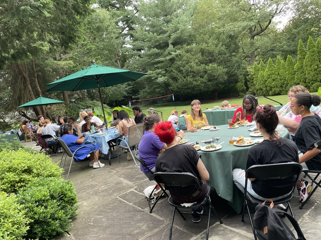 Students gathered around tables at the President's House