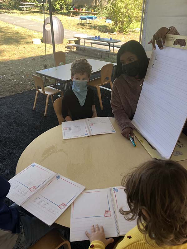 Teacher and students studying under a tent