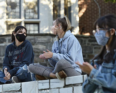 Students applauding while wearing masks