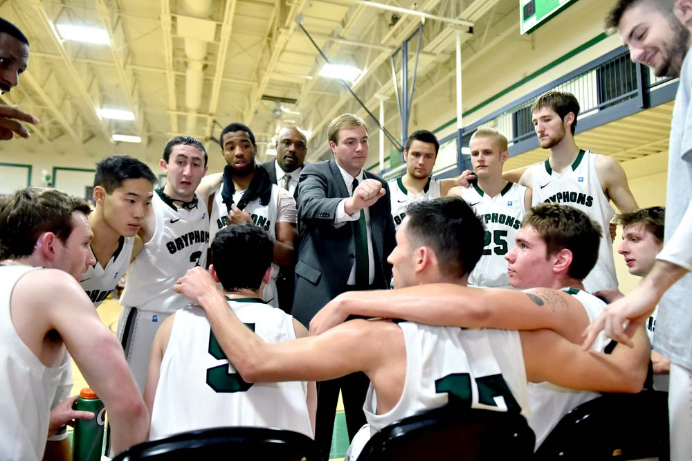 pic of a Homecoming basketball team in a huddle with the coach