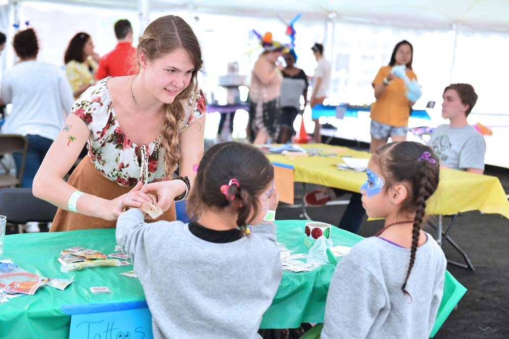 two children and a student providing a temporary tattoo sticker application at the Mayfair carnival