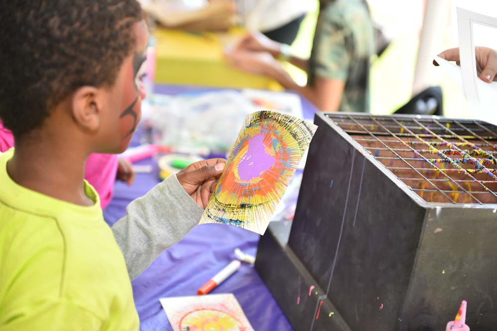 a young child holding their spin art at the Mayfair carnival