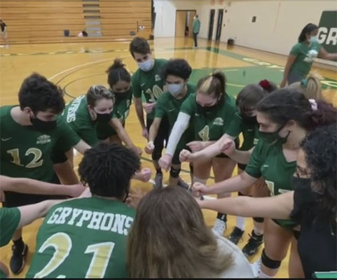 Volleyball team clasps hands in a huddle
